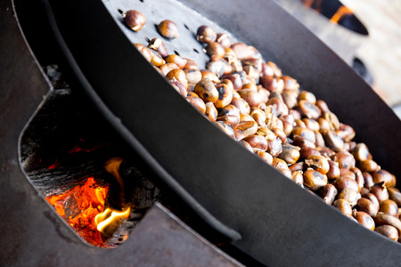 roasting pan: Organic Brown Chestnuts Roasting over a hot fire .