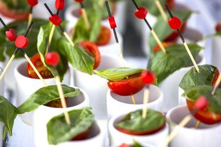Finger food: cherry tomatoes, mozzarella and basil. Wedding starter.