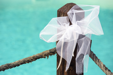 Wedding decoration. White bow with pool on background.