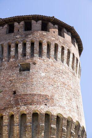 Tower of medieval italian castle on blue sky.