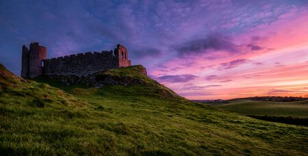 relish: Another sunset: Roche Castle staring at relish and pinkish Sunset in County Louth, Ireland Stock Photo