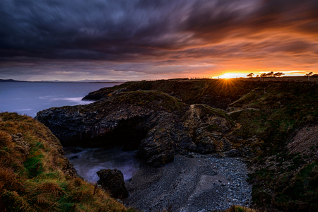 The glowing Eye: Far in the distance the Sun came staring at the Land from just under the Clouds layer in Portrane, County Dublin, Ireland Banco de Imagens