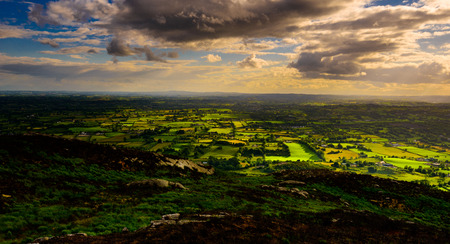 Stare of the Sun: in a very unsettled cloudy and rainy afternoon, from up high, we could see patches of Sun Light roaming the countryside, Croslieve, County Down, Northern Ireland, United Kingdom