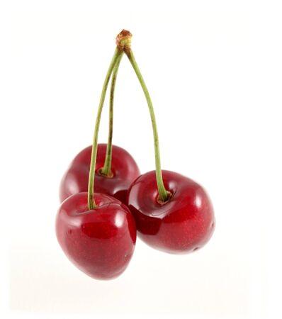 Three cherries on a white background photo