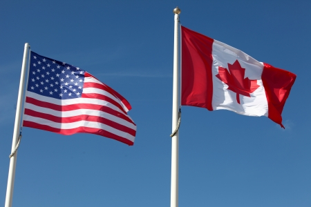 canadian state flag: American and Canadian flags waving against a cloudy sky Stock Photo