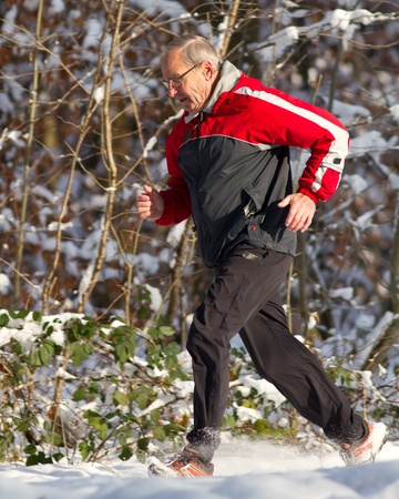 winter sports: senior running in the snow Stock Photo