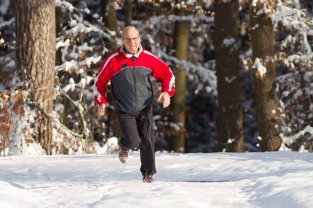 senior running in the snow Stock Photo