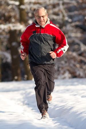senior running in the snow photo