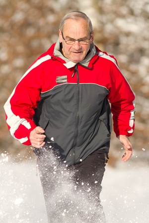 senior running in the snow photo