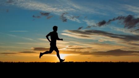 hombres corriendo: Corredores en la puesta de sol Foto de archivo