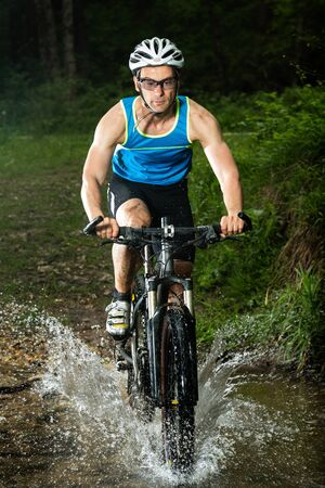 mountainbike: cyclist driving through a river Stock Photo
