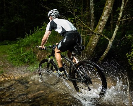 mountainbike: cyclist driving through a streambed