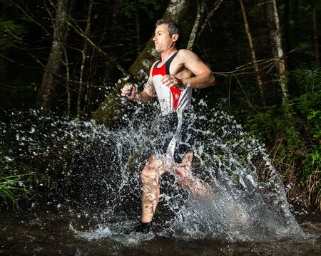 trail running: jogger in a streambed Stock Photo