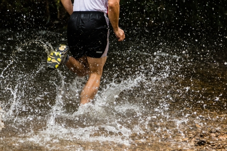 running water: trailrunner in a streambed