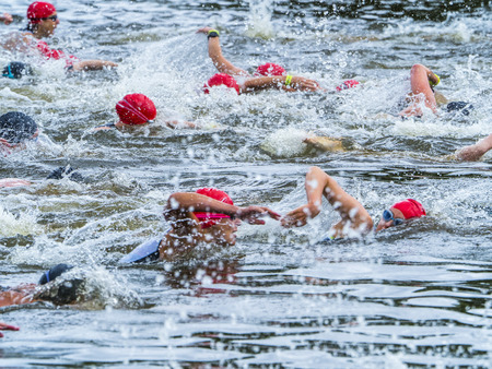 Group of triathletes swimming in a lake Stock Photo