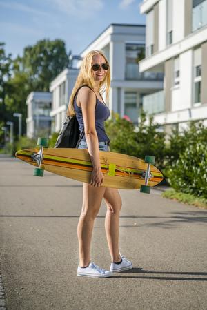 Young woman with a longboard in an urban area 版權商用圖片
