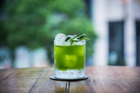 you can see a cocktail called gin basil smash standing on a table whose green color is strong and has a blurry background Archivio Fotografico