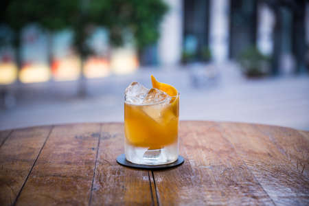 you can see a tasty yellow-colored cocktail on ice standing on a wooden table and the background is blurred 写真素材