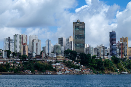 The cityscape of Salvador de Bahia, Brazil as seen from the ocean. A big contrast between the rich residential buildings and the poor favelas, slums.