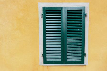 Modern green shutter on yellow plastered wall photo