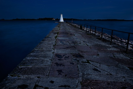 A small light house standing in the end of a pier in lake vättern by Vadstena town in sweden photo