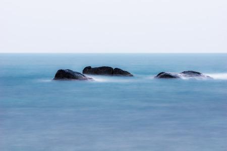 rocks water: Rocks in ocean with smoot water
