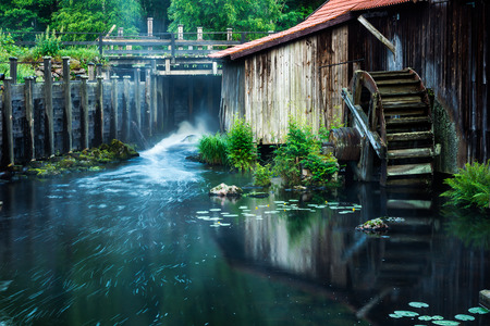 steelworks: old water wheel in stream by historic steelworks