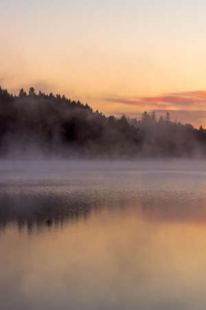 sunrise lake: colorful fall sunrise by a lake with mist over the water