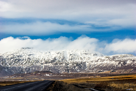 Road leading towards snow caped mountains