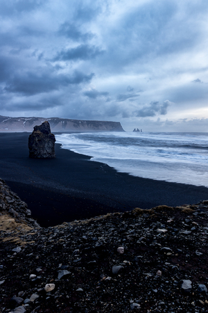 most: Rock on Black sand beach Dyrholaey Southern Iceland, With stom clouds in the sky