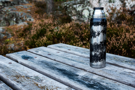 Old worn Thermos flask on wooden table outdoors