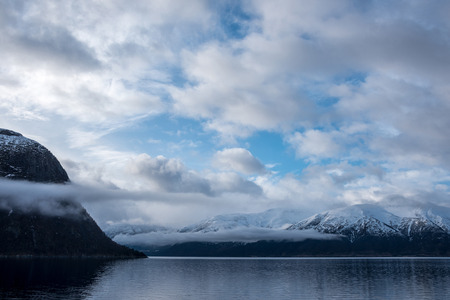 caped: Beautiful view of norwegian fjord, with blue sky and white clouds Stock Photo