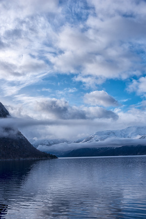 caped: Beautiful view of norwegian fjord, with blue sky and white clouds. Vertical composition