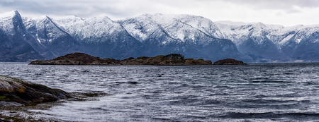 caped: Small island in Norwegian fjord with a snowy mountain range in the background