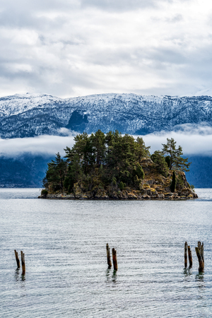 caped: Small tree covered island by snow caped mountain range Stock Photo