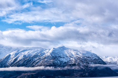 caped: Snow caped mountain range under a blue cloudy sky Stock Photo