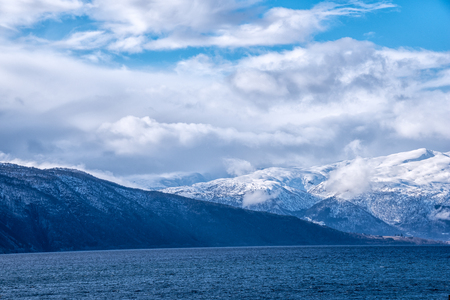 caped: Snow caped mountain range in Norway under a blue cloudy sky Stock Photo