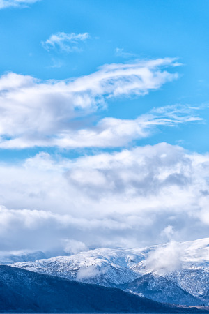 caped: Snow caped mountain range under a blue cloudy sky. Vertical composition