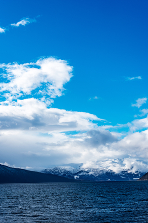 caped: view over fjord in Norway, with mountains in the background under a blue sky with white clouds