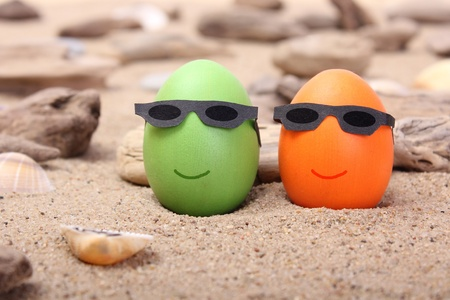 two Easter eggs with sunglasses on the beach