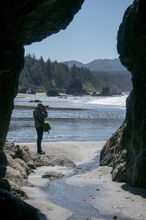 coastline: Man photographing coastline near cavern
