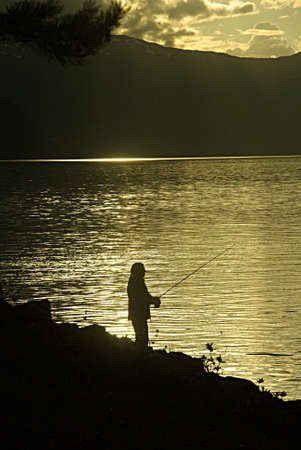 mysticism: Fishing man in the evening light by a fjord, Norway