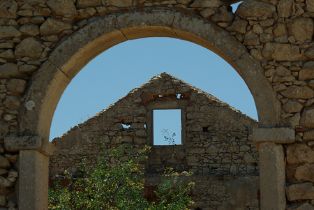 transience: View through archway to of a ruin on an old gable front