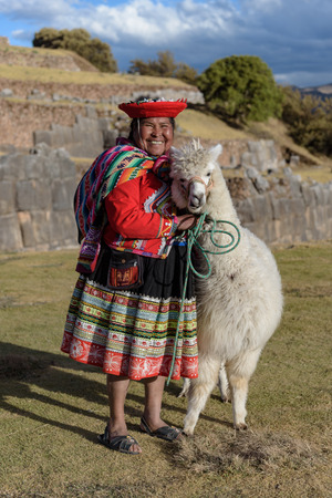Cuzco, Peru - July 14, 2018. Peruvian woman dressed in traditional colourful clothes with alpaca / llama at Sacsayhuaman, Cusco, Peru, South America.