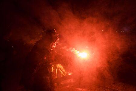 Kaprun, Salzburg/Austria - December 5, 2019: Krampus with fire and red smoke at traditional public show Krampuslauf in Kaprun. Stock Photo