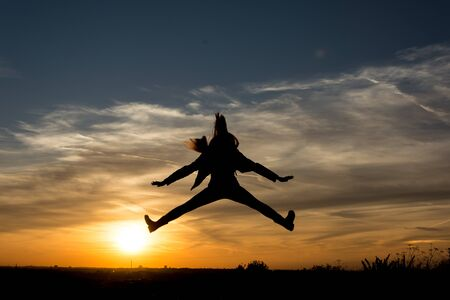 zest for life: People Silhouette Girl jumps in the sunset Stock Photo