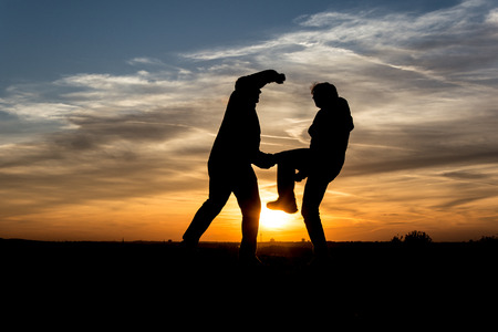 zest for life: People silhouette Two men fighting in the sunset