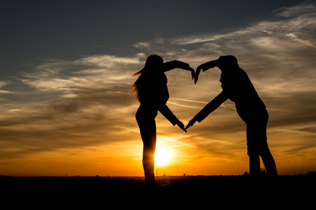 zest for life: People silhouette Mother and daughter forming a heart in the sunset