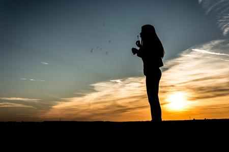 lebensfreude: Menschen Silhouette M�dchen machen Seifenblasen im Sonnenuntergang Lizenzfreie Bilder