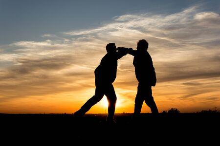 lebensfreude: Menschen Silhouette Zwei M�nner k�mpfen in den Sonnenuntergang